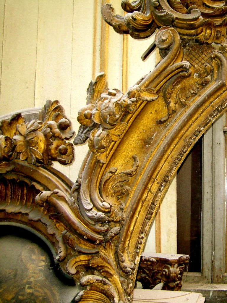 A GILDED FRAME ADORNED WITH THE CURVING FLORAL FORMS THAT CHARACTERIZE THE EARLY 18TH CENTURY ROCOCO STYLE